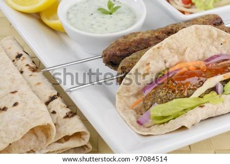 Seekh Kebab - Minced meat kebabs on metal skewers and as a wrap served with chili sauce, mint raita, crunchy salad, lemon wedges and chapatis.