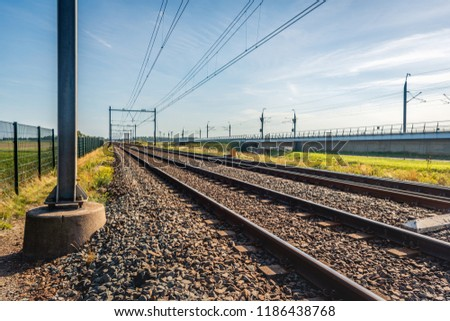 Seeminly endless train tracks on concrete sleepers and basalt gravel in the Netherlands. The photo was taken on a sunny summer day near the village of Lage Zwaluwe. In the background is the HSL line. #1186438768