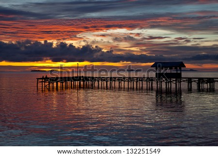 Seen from a Papuan village, the last sunlight of the day lights the clouds above the Dampier Strait in Raja Ampat, Indonesia.  This body of water is full of marine life and offers excellent diving. #132251549