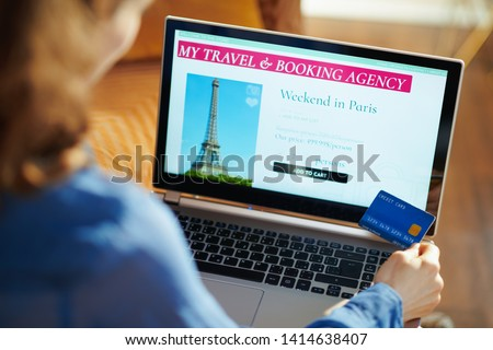 Seen from above young woman with opened on laptop online travel & booking agency site holding blue credit card at modern home in sunny summer day. A fake website is made for illustrative purposes. #1414638407