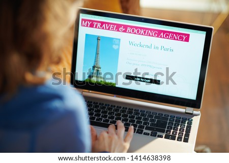 Seen from above young woman with opened on laptop online travel & booking agency site in the modern house in sunny summer day. A fake website is made for illustrative purposes. #1414638398