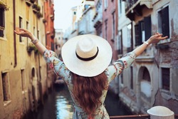 Seen from behind middle aged traveller woman in floral dress with hat in Venice, Italy.