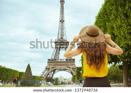 Seen from behind stylish solo tourist woman in yellow blouse and hat in Paris, France sightseeing.