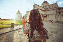 Seen from behind young solo tourist woman in floral dress with retro camera and backpack near Duomo di Pisa.