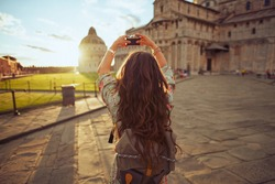 Seen from behind young woman in floral dress with vintage camera and backpack near Duomo di Pisa.