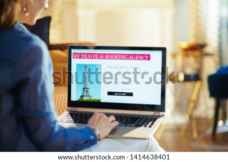 Seen from behind young woman with opened on laptop online travel & booking agency site in the modern house in sunny summer day. A fake website is made for illustrative purposes. #1414638401