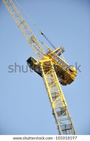seen from below and in evening sun a white bulding crane with winch and hook against a blue sky