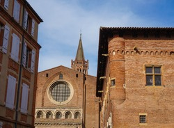 Seen from Emile Carthailac Street in the centre of Toulouse, in the South of France, behind a 16th century, brick Saint-Raymond building, the Western part of the Romanesque Basilica of Saint-Sernin