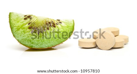 Segment kiwi and a handful of tablets on white. Isolation on white. Shallow DOF.