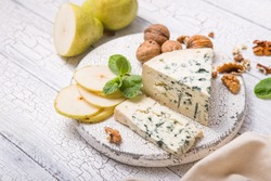 Segment of blue mould cheese - Gorgonzola with pear and walnuts on wooden board.  Top view