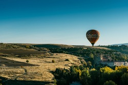 Segovia's landscape in sunrise with trees in golden hour and hot air balloons