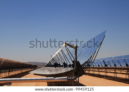 SEGS solar thermal energy desert electricity plant with parabolic mirrors concentrating the sunlight with blue sky copy space