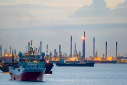 Seismic survey vessel and cargo container ships off the coast of Singapore Island Petroleum Chemical Refinery Plants