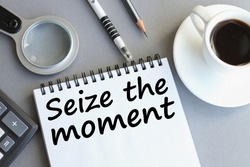 SEIZE THE MOMENT. text in notebook on gray background near magnifier, calculator. business concept