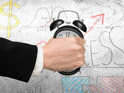Seizing the time and present opportunities concept. Businessman hand grasping alarm clock, with business concept doodles concrete wall background.