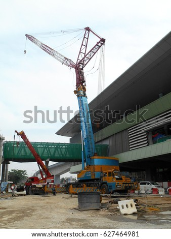 SELANGOR, MALAYSIA -OCTOBER 11, 2016: Mobile crane is the heavy machine used to lifting heavy material at construction site. Material was hang using strong and heavy duty cable.     #627464981
