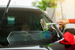 Selcective focus to staff using squeegee to clean the windshield. Car service in gas station.