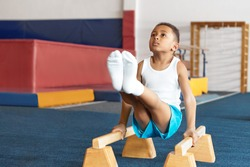 Seld determined disciplined African American little sportsman in white t-shirt, socks and blue shirts training on two wooden parallel bars, lifting legs. Fitness, childhood and artistic gymnastics