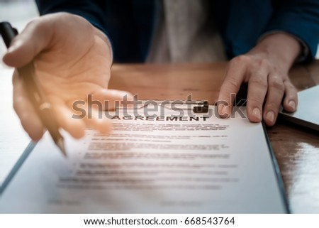 select focus agreement paper,estate agent gives pen and documents agreement with customer to sign contract. Concept agreement #668543764