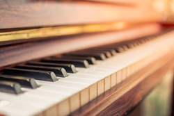 Select focus and soft focus.Close-up of a wooden piano set near a window to receive warmth from the sunshine in the morning of winter in Thailand. The most melodious musical instrument in a beautiful