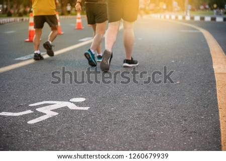 Select focus, healthy mature people jogging  on track for jogging in the park at evening with sunset in background,  - Image #1260679939