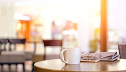 Select focus hot coffee cup in morning with newspaper and glasses at cafe with wood table