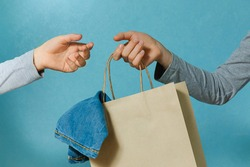 Select focus of one hand of the child is passing a craft paper bag with blue jeans to the other hand. Concept of thrift stores, resale, second hand.
