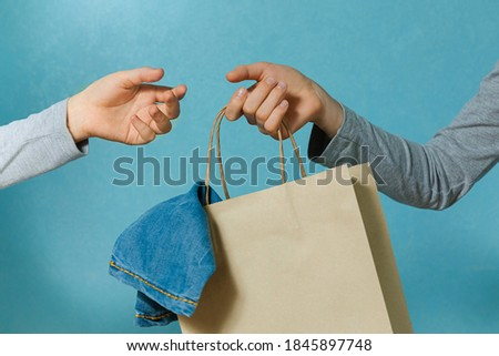 Select focus of one hand of the child is passing a craft paper bag with blue jeans to the other hand. Concept of thrift stores, resale, second hand. Foto stock ©