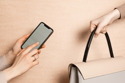 Select focus of one woman's hand  is passing a grey bag and another girls hands with smartphone is  pointing to clear screen. Concept of thrift stores, resale, second hand, resale application.