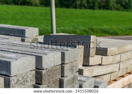 Selected focus and close up sunny view on stack of concrete blocks lie beside street and green agricultural field in countryside atmosphere. Pile of concrete blocks at construction site. #1415508026