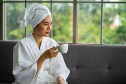 selected focus Asian young attractive woman wearing white bath robe sitting for Spa massage service.