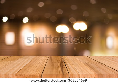 Selected focus empty brown wooden table and Coffee shop blur background with bokeh image. for your photomontage or product display. #303534569