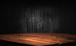 Selected focus empty brown wooden table and wall texture or old black brick wall blur background image. For your installation or product demonstration
