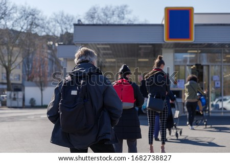 Selected focus, European people queue on street outside supermarket during quarantine for COVID-19 virus in Düsseldorf, Germany.