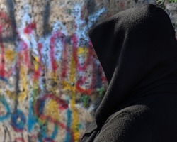 Selected Focus of a frightened woman in black dress with unrecognizable face turned back in front of a graffiti Painted Wall, Copy Space.
