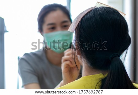 Selected focus on Model for makeup. Makeup artist wearing face mask doing makeup for girl indoor during Covid 19. Makeup artist doing make up for young beautiful bride.