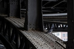 Selected focus, pigeon bird stand on old black arch steel structure under the bridge.