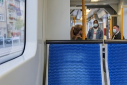 Selected focus view at blue seat on the Light rail tram and blur background of passengers wear face mask protection during epidemic of COVID-19 in Düsseldorf, Germany.