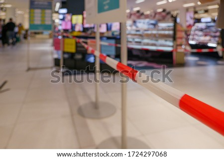 Selected focus view at Red and white caution tape restrict shelves and booth area inside store in Germany during social distancing and global quarantine. COVID-19 restrictions on Shopping mall. Foto d'archivio ©