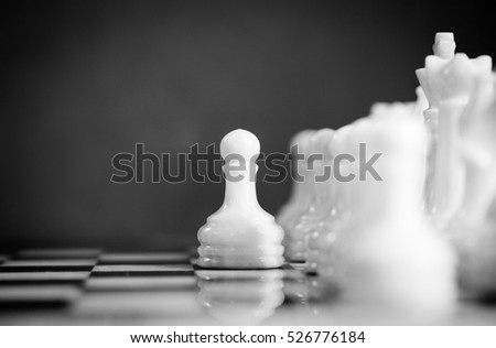 Selected focused chess set. White go the first, pawn moves one step forward. The central figure-pawn is on focused. Teamwork concept. Chess game. Black & White.