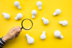 Selected great ideas concepts with male hand using magnifying glass looking for group of lightbulb on color background.Business creativity.human performance