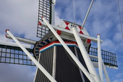 Selected parts of an ancient dutch windmill against a blue sky with some clouds