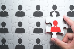 Selecting right people for organization's success. Human resource management and selecting leader concept. Putting last jigsaw puzzle piece with red businessperson.