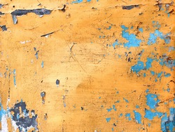 Selection focus, Old yellow peeling paint on blue wall texture. Steel metal wall background.