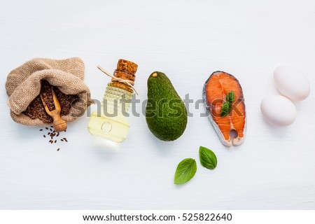 Selection food sources of omega 3 and unsaturated fats. Super food high vitamin e and dietary fiber for healthy food. Flax seed in hemp sack bag,olive oil ,fish oil ,salmon and white eggs on white.