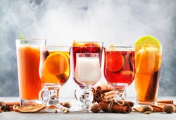 Selection of autumn or winter alcoholic hot drinks and cocktails - mulled wine, glogg, grog, eggnog, warm ginger ale, hot buttered rum, punch, mulled apple cider on gray background, copy space