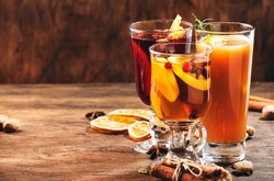 Selection of autumn or winter seasonal alcoholic hot cocktails - mulled wine, glogg, grog, eggnog, warm ginger ale, hot buttered rum, punch, mulled apple cider on wood background, copy space