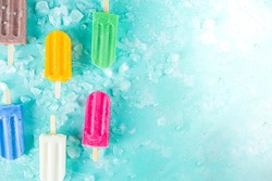 Selection of bright multicolored ice cream popsicle. Various gelato, frozen lollypops - chocolate vanilla blueberry strawberry pistachio orange, with crushed ice on light blue sunny background