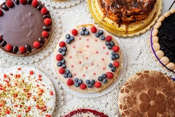 selection of cheesecakes, profiterole, carrot cake, tartlet, fruit cakes for mothersday, valentines day on white background