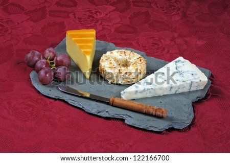 Selection of cheeses on a Welsh slate cheese board comprising of Smoked Irish Cheddar, Danish soft cheese coated with pineapple and almonds and Gorgonzola.